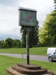 The village sign at Cavendish in Suffolk depicting events from the Peasants' Revolt.